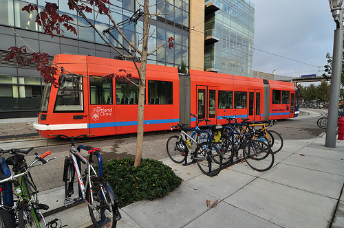 Streetcar in the South Waterfront District flanked by many parked bikes