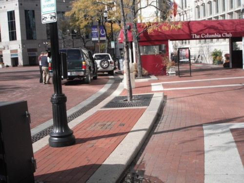 Gentle curbs punctured with ADA-compliant openings minimize the hierarchical relation between pedestrians and cars.
